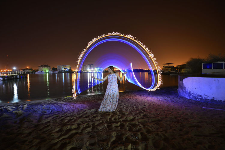 Blurred motion of woman on illuminated land against sky at night