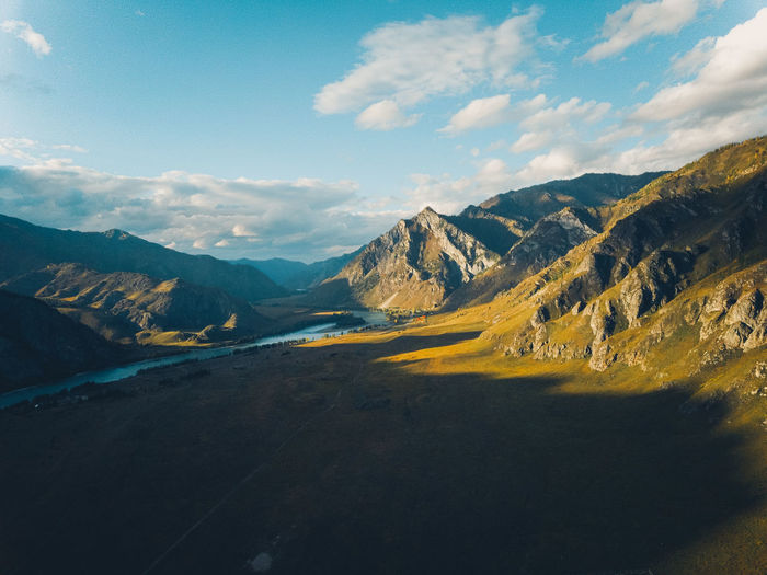 Bright yellow textured mountains against a blue sky, aerial view. sunset. drone shot