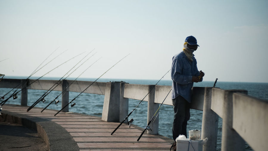 Fishing Pole Day Fisherman Fishing Lifestyles Looking At View Men Nature One Person Outdoors Real People Sea Sky Standing Water