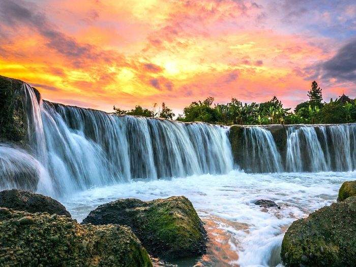Waterfall Tourism Scenics Travel Vacations Social Issues Travel Destinations Beauty Water Motion Tourist Nature Sunset Landscape Beauty In Nature Environmental Conservation Long Exposure River Outdoors Stream - Flowing Water Bekasi Parigi Waterfall At Bekasi Parigi Waterfall