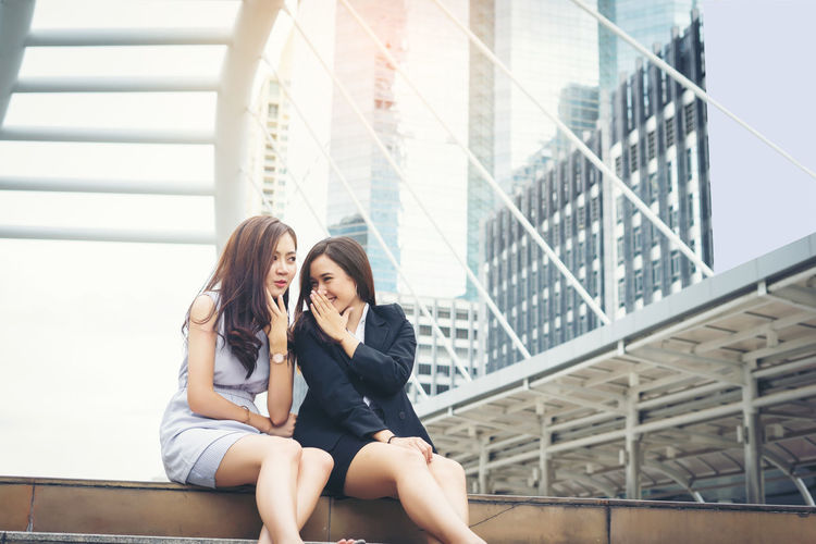Smiling young woman whispering something with friend while sitting on steps in city