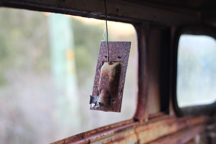 Close-up of rusty metal hanging against window