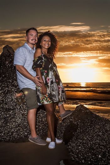 Full Length Portrait Of Young Couple Standing On Shore At Beach Against Sky During Sunset