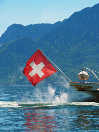 Swiss Flag On Boat In Lake Against Mountains