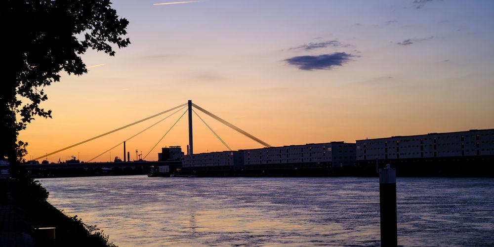 Silhouette bridge over river against sky during sunset