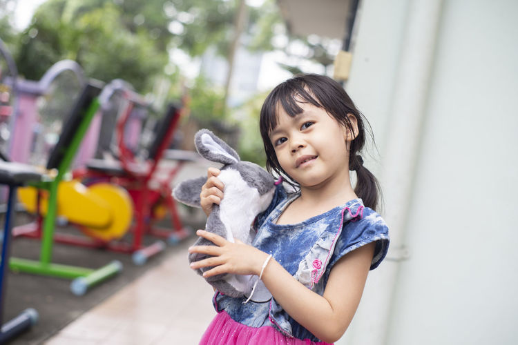 Portrait of cute girl holding stuffed toy while standing outdoors