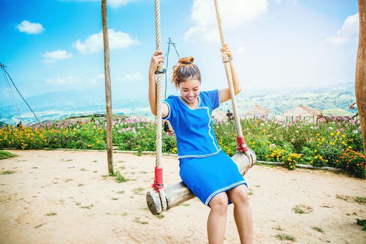 Full length of smiling girl on swing against sky