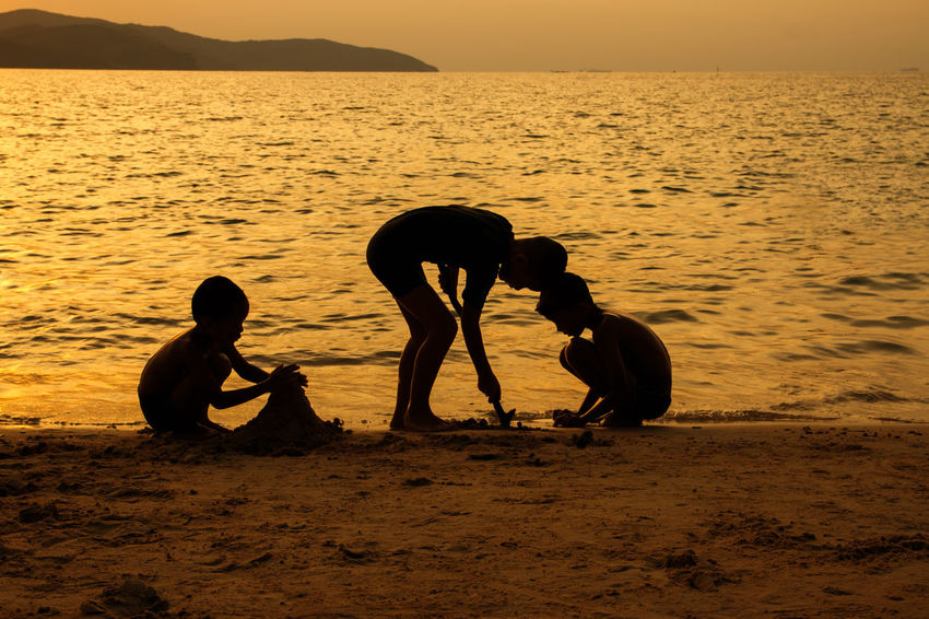 silhouette of people at the beach,The beauty of natural light at sunset. Real People Water Sky Beach Sea Sunset Land Beauty In Nature Nature Men Scenics - Nature Togetherness Leisure Activity People Lifestyles Silhouette Sitting Outdoors Silhouette Happiness Happy Holiday Relaxing Children Women Man Romantic Orange Clouds And Sky Love Family Summer Sunrise Boy Freshair Freedom Fun