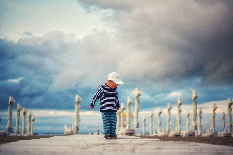 The little cute boy and the storm on the beach