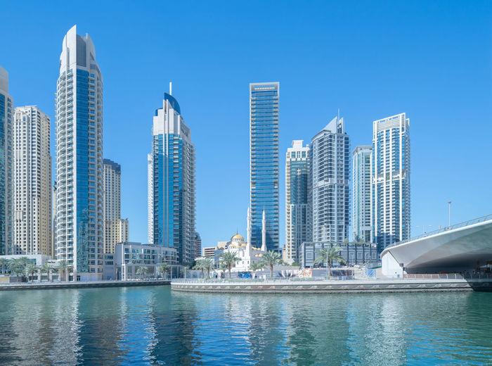 Modern buildings by swimming pool against blue sky