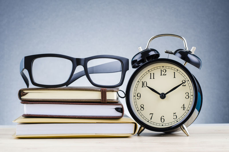 alarm clock, and spectacles on stacking book over dark background, Clock Alarm Clock Glasses Time Table Still Life Eyeglasses  Publication Indoors  No People Book Stack Number Close-up Education Studio Shot Group Of Objects Personal Accessory Accuracy Clock Face Minute Hand
