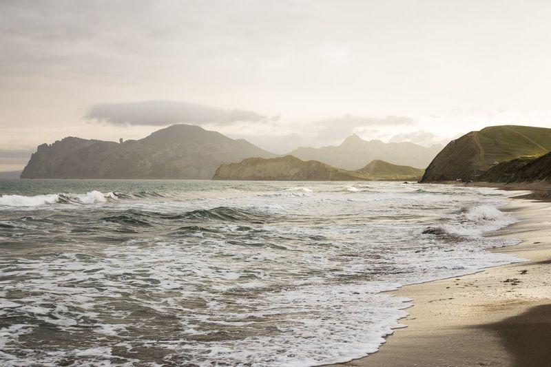 Dramatic seascape with mountain range at the horizon