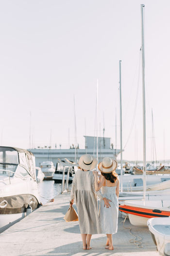 Two women friends walk along the pier along the boats and yachts