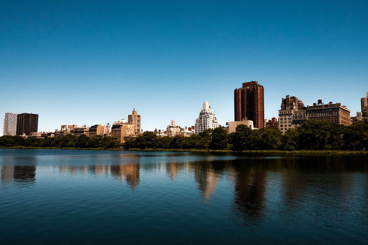 Scenic view of river by buildings against clear blue sky
