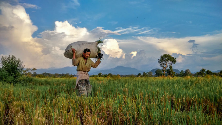 Farmer Carrying Sack Of Crops On Field Against Sky