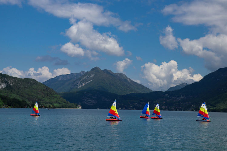 People on sailboat in sea against mountains