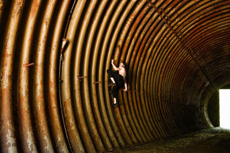 Full length of man climbing on metallic wall