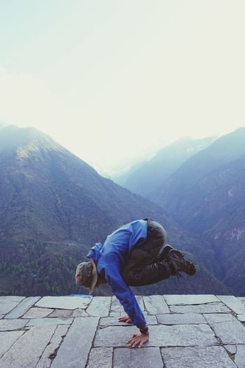 Side view of woman doing handstand on stone