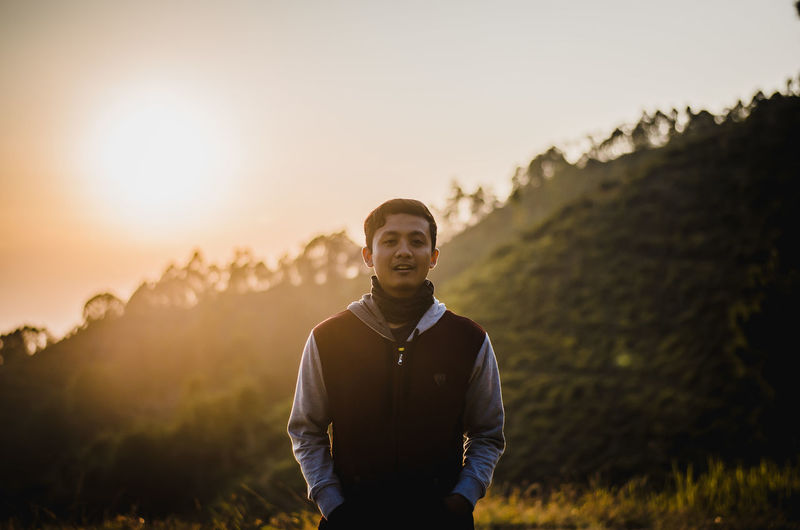 Portrait of young man standing on field during sunset