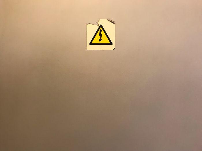 Danger sticker on gray wall background with copy space Single Object Old Gray Simbol Sign Warning Dangerous Danger Sign Communication Wall - Building Feature Triangle Shape Shape No People Symbol Yellow Copy Space Indoors  Arrow Symbol Geometric Shape Warning Sign Information Information Sign Guidance High Voltage Sign Electricity  Warning Symbol