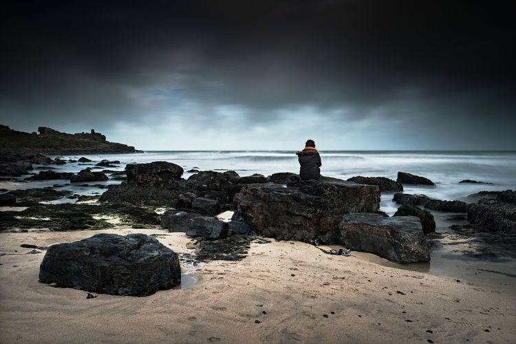 Rear view of man looking at sea shore against sky