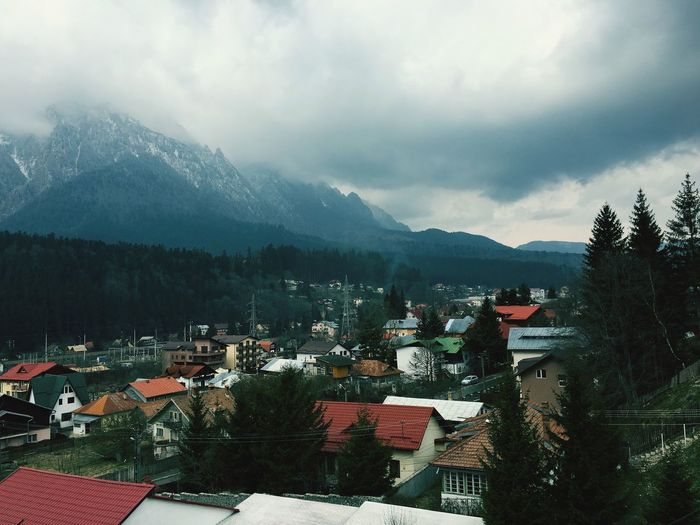Houses against mountains and cloudy sky