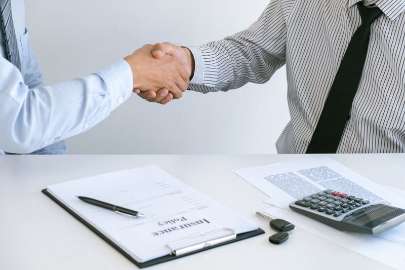 Midsection of agent giving handshake to customer in office
