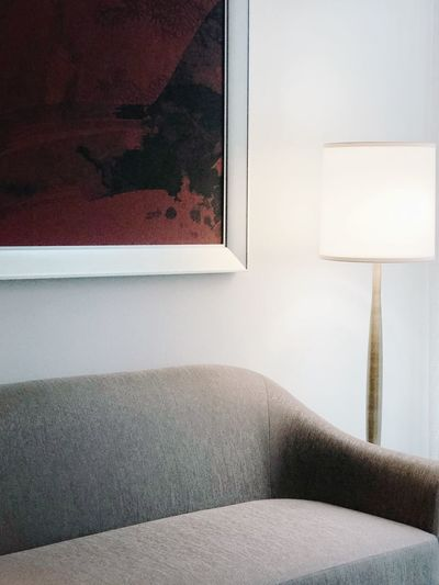 Illuminated lamp by painting over sofa at home