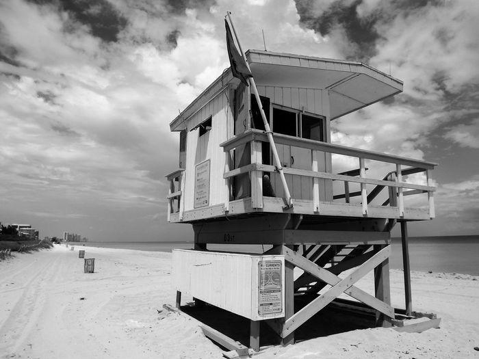 Lifeguard hut against cloudy sky