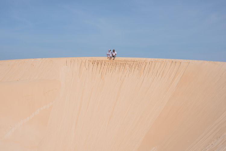 Couple sitting at edge of sand dune
