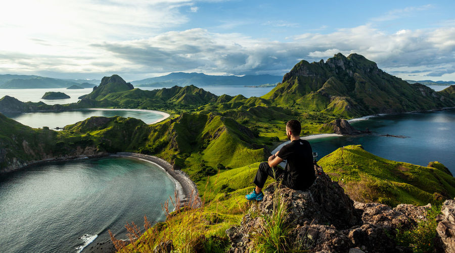 A man sitting on the rock on top of padar island