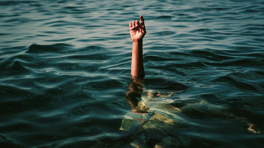 Cropped hand of man swimming underwater