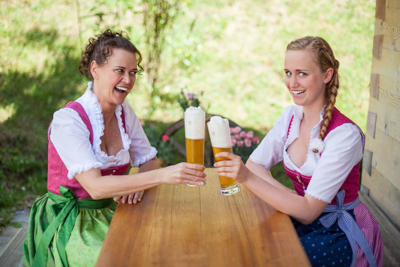 Mother and daughter sitting on a mountain pasture in the Bavarian dirndl festive at a table and have a glass of beer poured. Alm Bavaria Family Fun Mother Munich Oktoberfest Thirst Bavarian Beer Garden Beer Glass Bunches Comfortable Daughter Dirndl Girls Holliday Laugh Leisure Activity Outdoors Table Traditional Two Wheat Beer Women