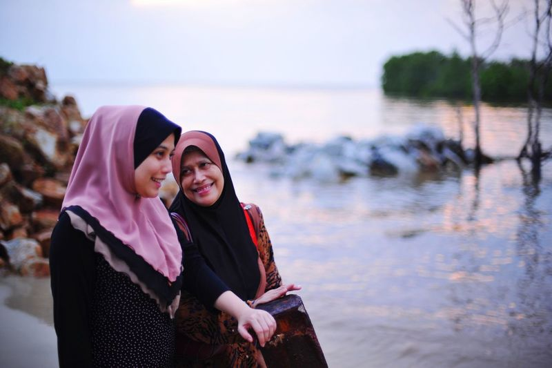 Smiling mother with daughter in hijab standing at beach against sky during sunset