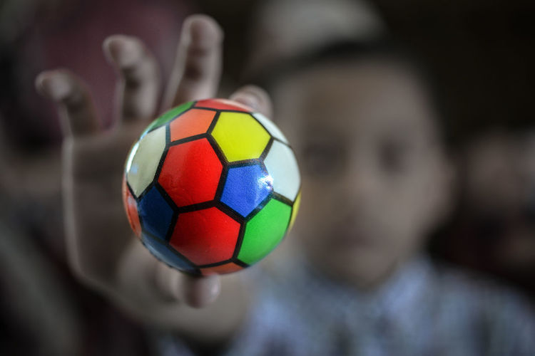 Defocused Image Of Girl Holding Colorful Ball