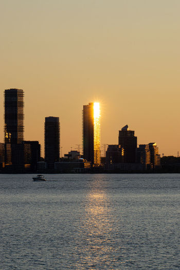 Sea by buildings against clear sky during sunset