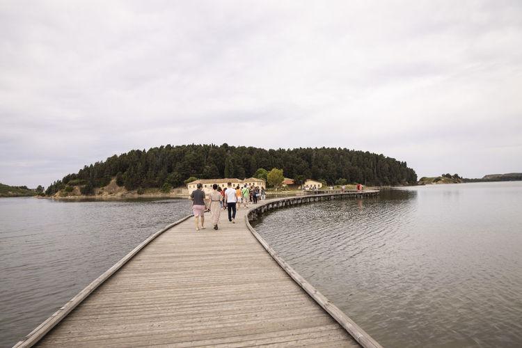 Rear view of people walking on lake against sky