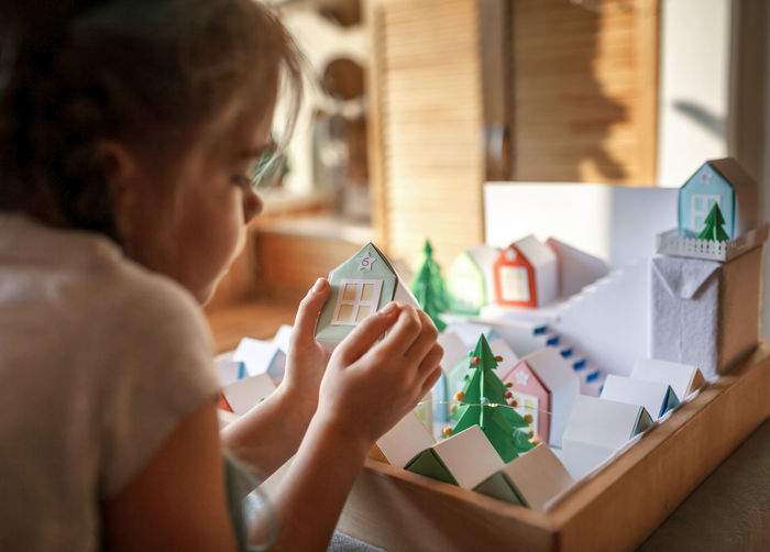 Origami advent calendar, paper craft. girl looking upon paper houses with number and paper tree