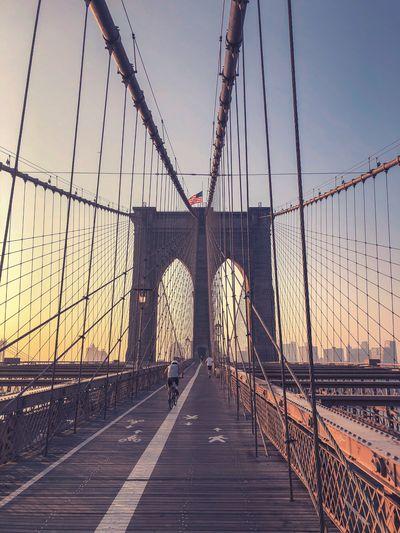 Brooklyn bridge against clear sky during sunrise