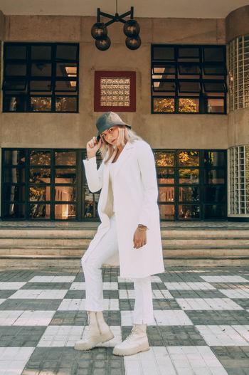 Full length of woman standing on floor against building