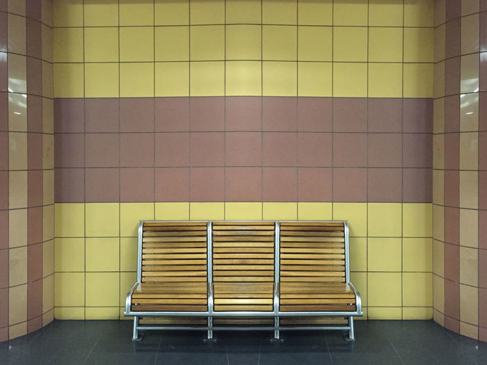 Empty bench against tiled wall at subway station