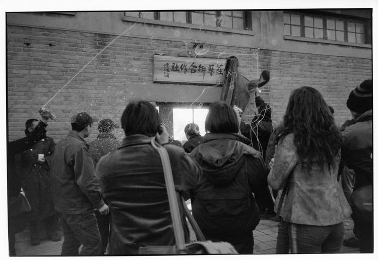 2001时,片山在宋庄开了个黔味饭店,在饭店的二楼设了一个小展厅。是宋庄唯一的公共正式展览场所。第二次做展时即被当地政府机构多部门联合禁展。除外宋庄再无可供展览的场所,当时即使是北京市区里也没有多少画廊。直到2003年冬,宋庄艺术合作社成立,宋庄才有了另一个正式展览场所。宋庄艺术合作社在远离小堡的关辛庄。由艺术家张海鹰的姐姐张海燕,出资承租下一处早已废弃多年不用的供销合作社做为展馆。有4、5位艺术家居住创作于此。评论家栗宪庭揭幕。直到05年宋庄艺术促进会成立,并勒令其停止一切展览活动。其存在的两年多中,是宋庄艺术家展出作品与观展的唯一去处。一度很是人气旺盛。图为开幕时烤全羊。2003年冬。 1613 10909308 12820764