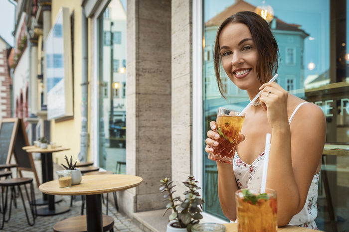 young woman having ice tea Dress Happiness Reflection Summer Exploratorium Beautiful Woman Brunette Girl  Cafe Caucasian Drink Enjoying Life Food And Drink Happiness Holding Ice Tea Indoors  One Person Outdoors Refreshment Smiling Straw Table Window Women Young Adult Young Adults
