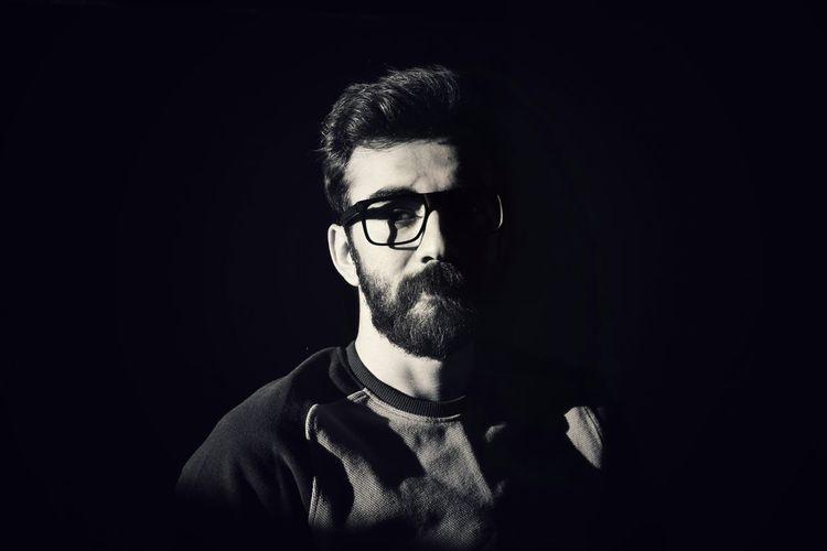 Young man wearing eyeglasses against black background