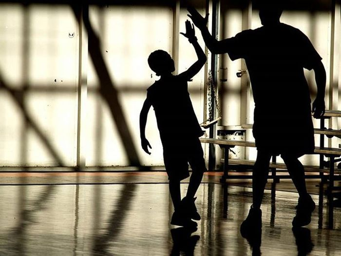 Silhouette of father son giving high-five