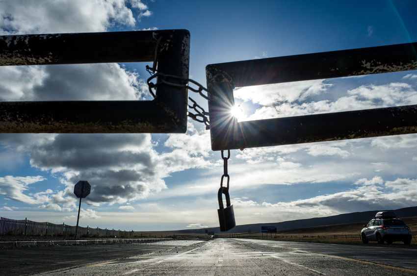 Closed Border Crossing between Chile and Argentina Blockade Border Crossing Chile Argentina Barrier Border Car Chain Link Cloud - Sky Day Direction Land Vehicle Lens Flare Lock Mode Of Transportation Nature No People Outdoors Road Sky Sun Sunbeam Sunlight The Way Forward Transportation