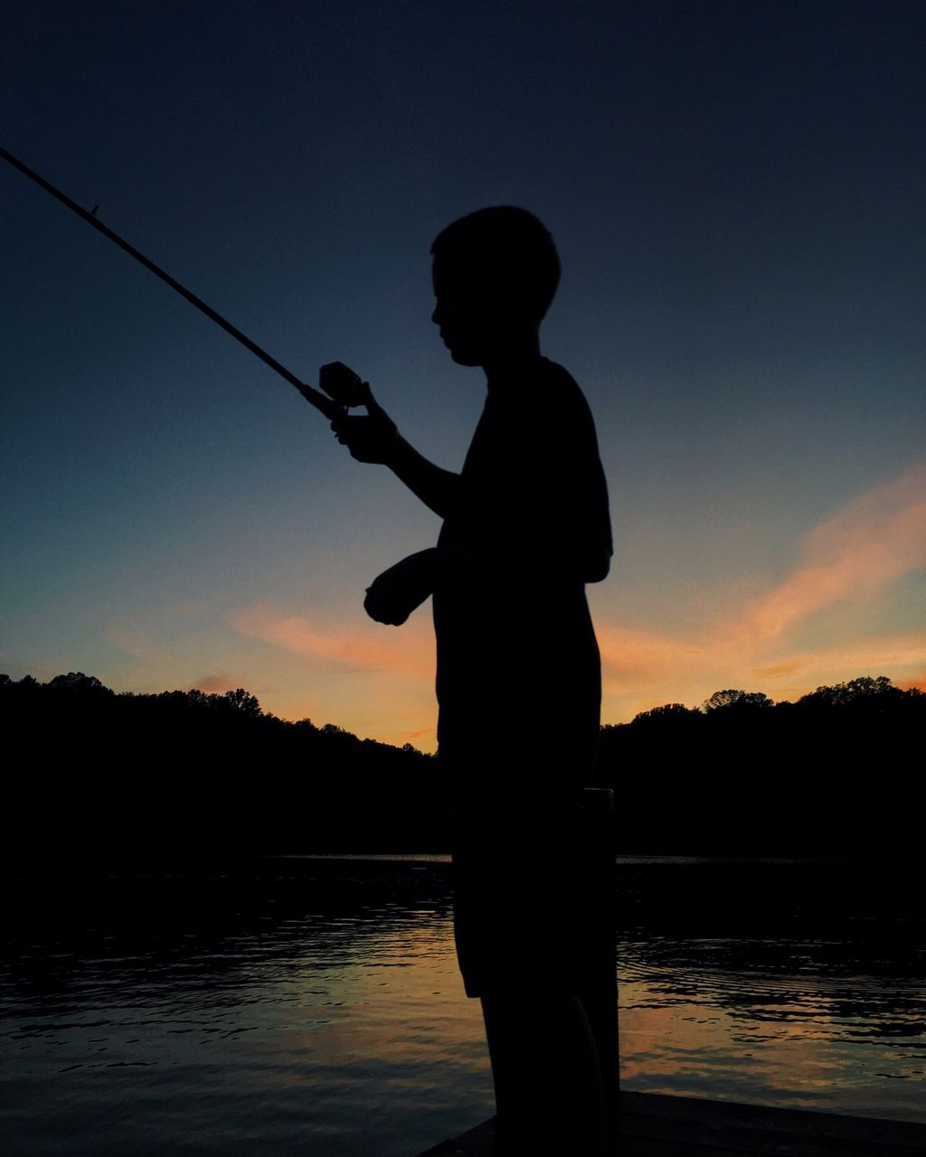 Silhouette Man Fishing By River Against Sky During Sunset