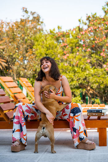 Young woman with dog sitting outdoors