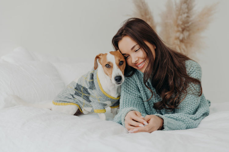 Smiling woman with dog relaxing on bed