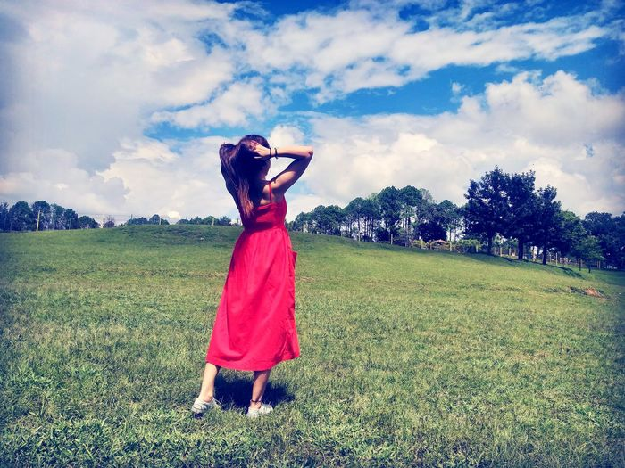 Woman in red dress standing on field.